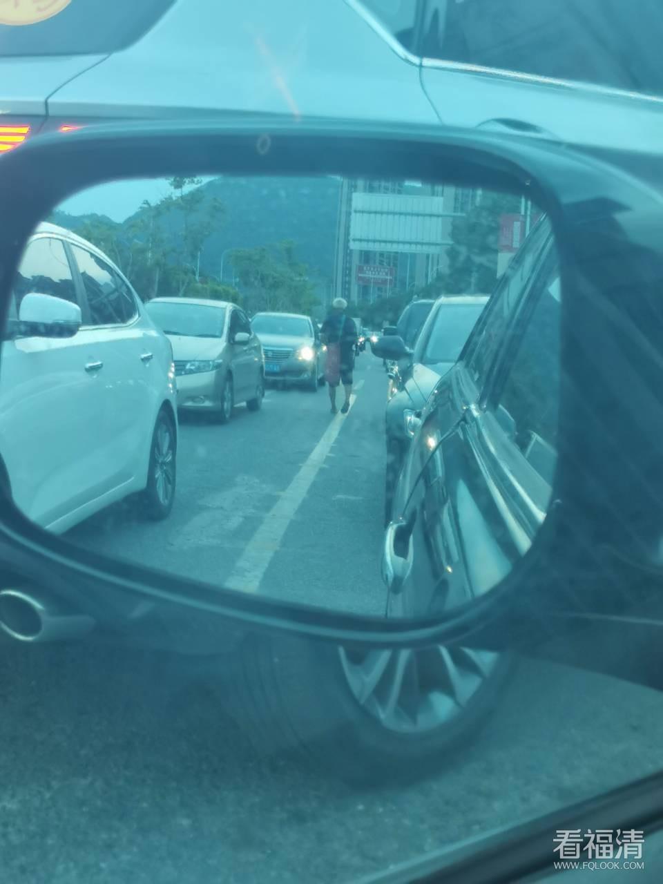 在观音上隧道前那个红绿灯发现一名老人家在机动车道行